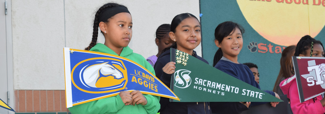 Natomas Park students holding up college pennants at the college assembly