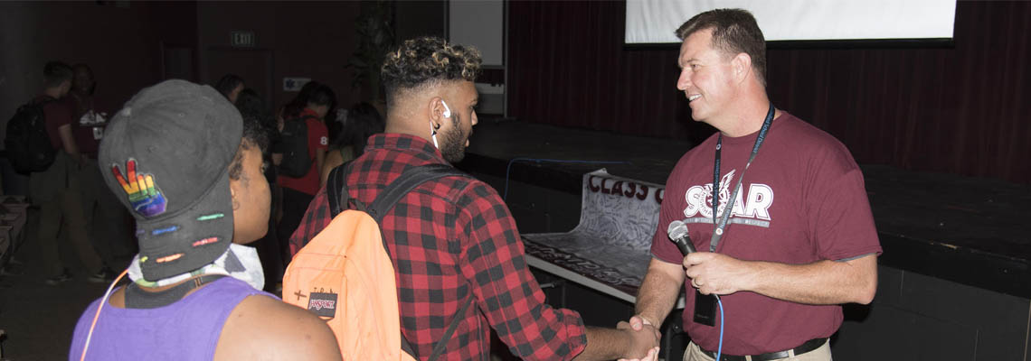 Principal Scott Pitts shaking hands with one of his students