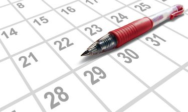 Dates on a calendar with red pen sitting on top