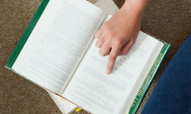 Finger pointing at page in book