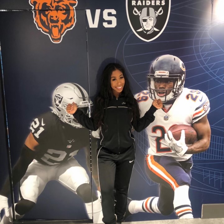 Inderkum High School Alumni Danielle McCarthy pointing at poster with football players